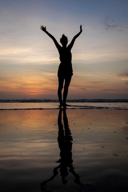 Siluetta di una ragazza che sta nell'acqua con le sue braccia alzate Foto Gratuite