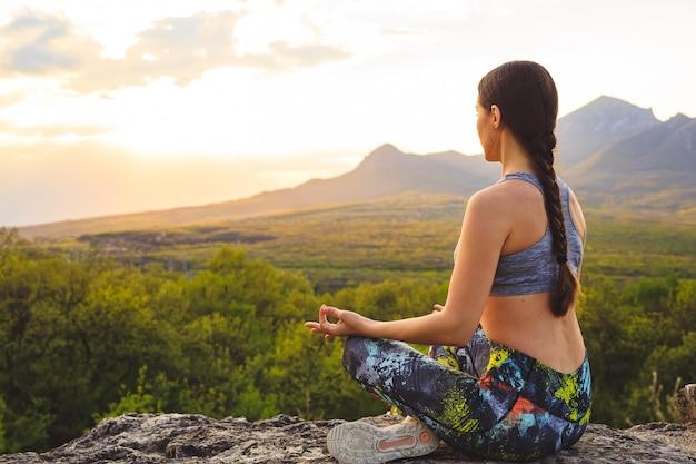 Siluetta di yoga di pratica della giovane donna al tramonto Foto Premium