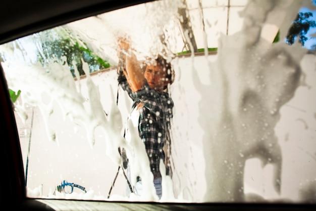 Siluetta poco chiara dell'uomo che lava un finestrino della macchina Foto Gratuite