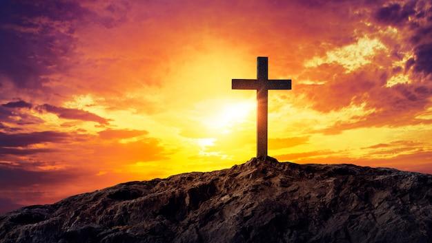 Siluetta trasversale cristiana proiettata sulla montagna al tramonto Foto Premium