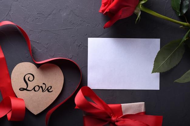 Simboli di amore della cartolina d'auguri del fondo di san valentino, decorazione rossa con i regali delle rose del cuore di vetro su fondo di pietra. vista dall'alto con spazio di copia e testo. superficie piana Foto Premium