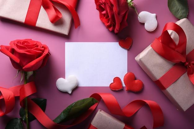 Simboli di amore della cartolina d'auguri del fondo di san valentino, decorazione rossa con i regali delle rose del cuore di vetro su fondo rosa. vista dall'alto con spazio di copia e testo. superficie piana Foto Premium