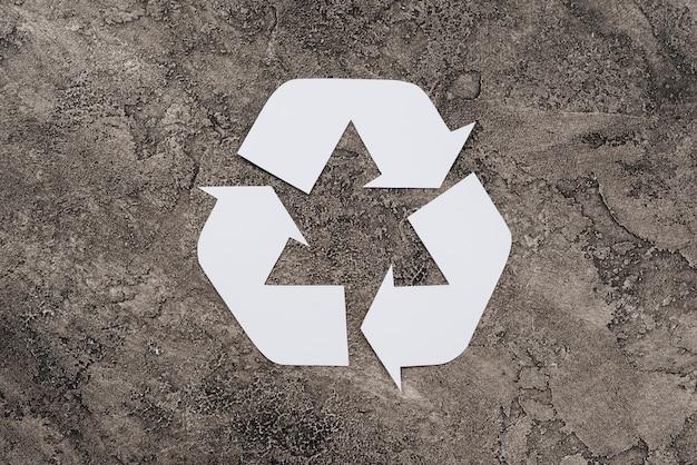 Simbolo bianco di riciclaggio su sfondo sporco Foto Gratuite