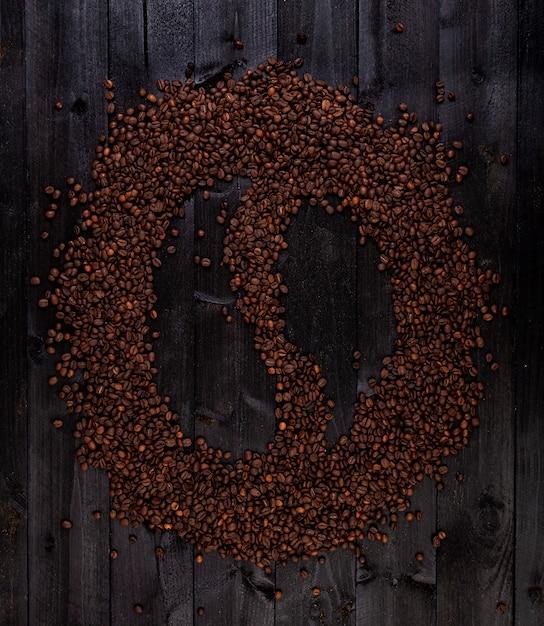 Simbolo del caffè fatto di chicchi di caffè tostati su un legno nero Foto Premium