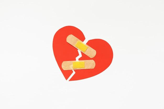 Simbolo del cuore rosso rotto con patch medica, concetto di amore. guarigione. copyspace Foto Premium