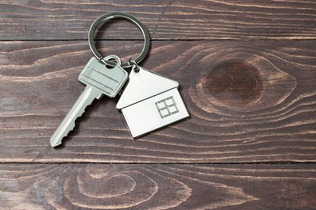 Simbolo della casa con chiave d'argento su fondo in legno d'epoca Foto Premium