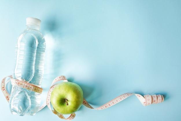Simbolo di dieta piatto disteso un metro nastro e mela verde e bottiglia d'acqua. Foto Premium