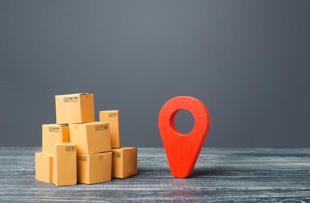 Simbolo di geolocalizzazione del puntatore di posizione rosso e scatole di cartone Foto Premium