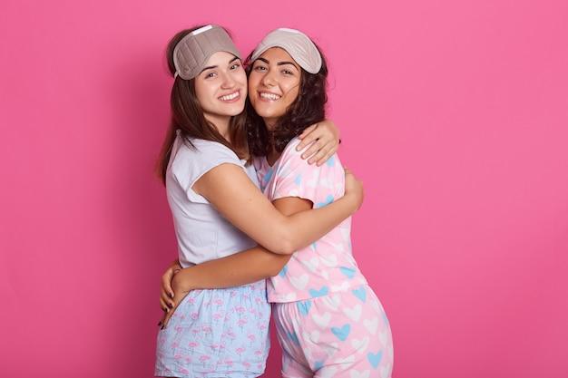 Sinceri amici belli in posa isolato su rosa, abbracciati, sorridenti Foto Gratuite