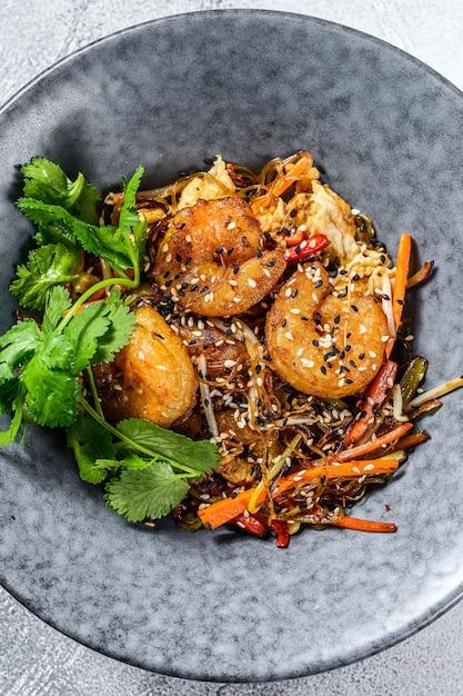 Singapore mei fun. tagliatelle di riso con gamberi, gamberi, carne di maiale, carota, cipolla, cavolo di napa. sfondo bianco. vista dall'alto Foto Premium