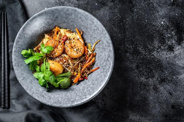 Singapore mei fun. tagliatelle di riso con gamberi, gamberi, carne di maiale, carota, cipolla, cavolo di napa. sfondo nero. vista dall'alto. copia spazio Foto Premium