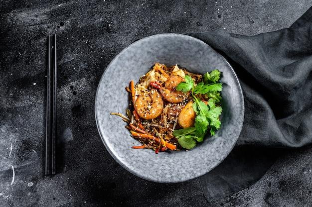 Singapore mei fun. tagliatelle di riso con gamberi, gamberi, carne di maiale, carota, cipolla, cavolo di napa. sfondo nero. vista dall'alto Foto Premium