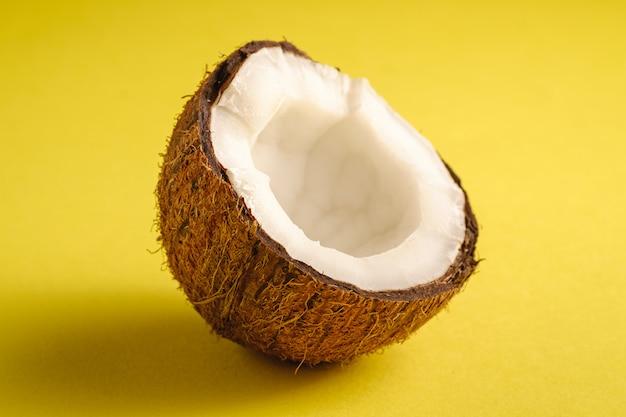 Singola frutta della noce di cocco sulla superficie normale gialla, concetto tropicale dell'alimento astratto, macro di vista di angolo Foto Premium