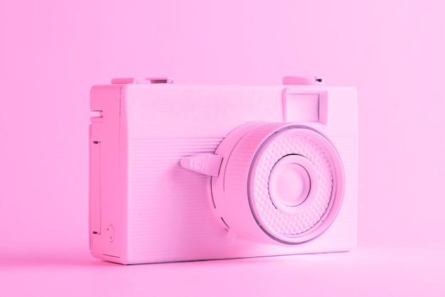 Singola macchina fotografica verniciata contro il contesto rosa colorato Foto Gratuite