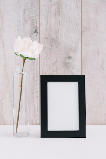 Singolo fiore bianco in vaso vicino alla cornice in bianco Foto Gratuite