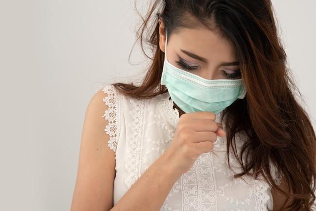 Sintomo di raffreddore o di allergia di influenza, giovane donna asiatica ammalata che starnutisce nell'isolato della mascherina su bianco Foto Premium