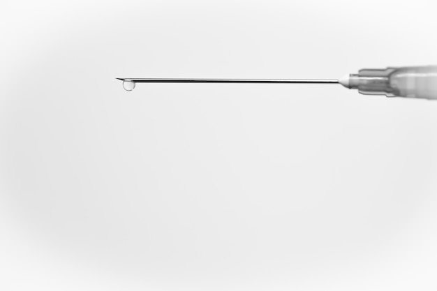 Siringa medica bianca con una goccia, isolata su bianco Foto Gratuite