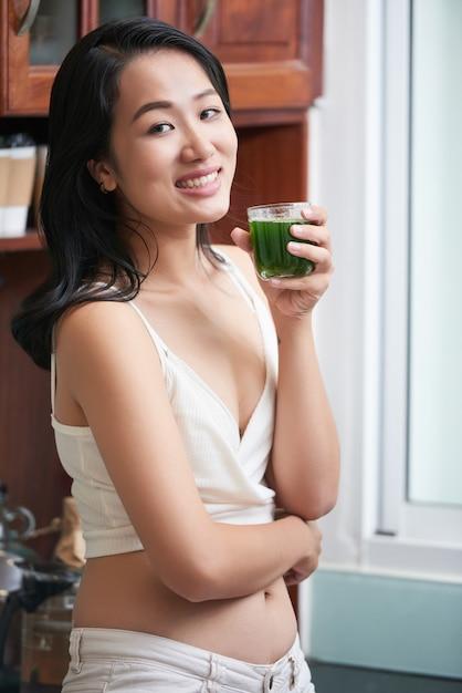 Slim donna etnica con un bicchiere di succo Foto Gratuite