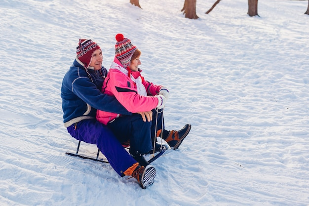Slitta. coppia senior in slitta. famiglia divertendosi a winter park. san valentino. attività invernali Foto Premium