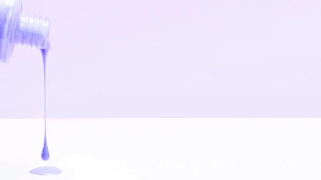 Smalto viola che gocciola dalla bottiglia sul contesto bianco Foto Gratuite