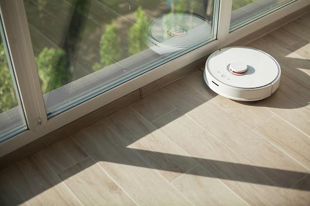 Smart house, robot aspirapolvere gira sul pavimento di legno in un salotto Foto Premium