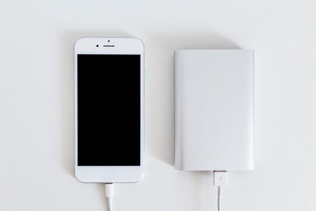 Smart phone collegato con caricabatterie banca di potere su sfondo bianco Foto Gratuite