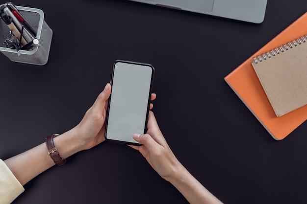 Smart phone della tenuta della mano della donna con lo schermo in bianco dello spazio della copia. Foto Premium