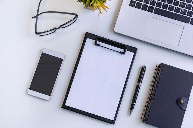 Smart phone e compressa dello schermo vuoto con il computer portatile sull'ufficio dello scrittorio di affari con lo spazio della copia, vista superiore Foto Premium