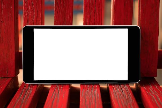 Smart phone mobile con lo schermo in bianco su legno rosso. tecnologia e concetto di stile di vita. Foto Premium