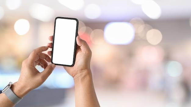 Smart phone mobile nella mano dell'uomo al lavoro di scrivania. Foto Premium