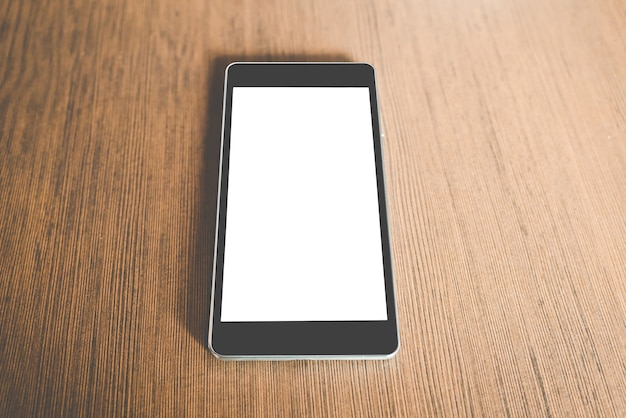 Smart phone nero con schermo vuoto nella tabella di legno. concetto di tecnologia. Foto Premium