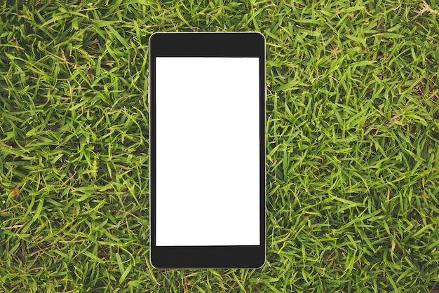 Smart phone nero con schermo vuoto sull'erba Foto Premium