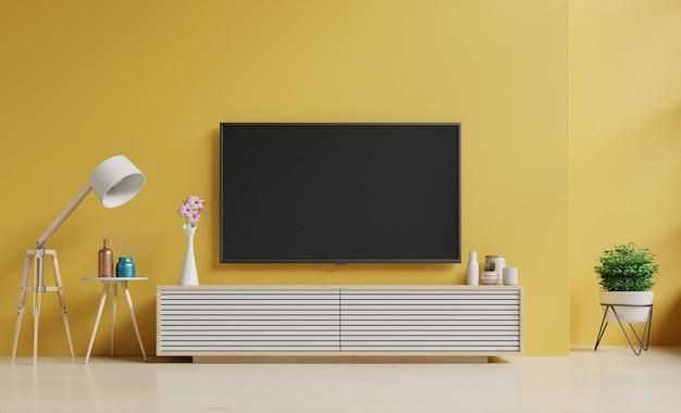 Smart tv sul muro giallo nel soggiorno e lampada da terra, dal design minimale Foto Premium
