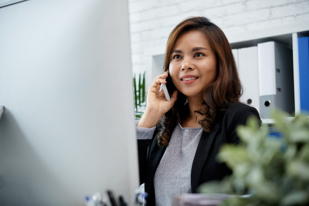 Smartphone asiatico sorridente della tenuta di signora di affari all'orecchio e allo schermo di computer Foto Gratuite