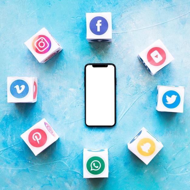 Smartphone circondato da blocchi di applicazioni per social media Foto Gratuite