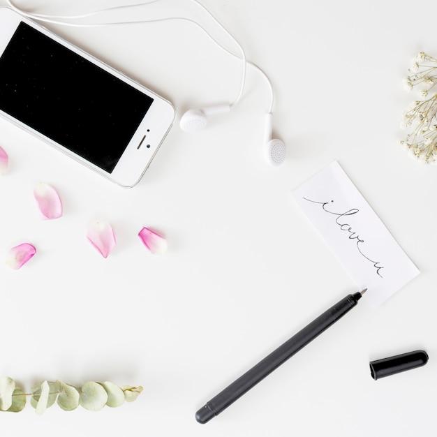 Smartphone con auricolari vicino tag con titolo, penna, petali di rosa freschi e ramoscelli di piante Foto Gratuite