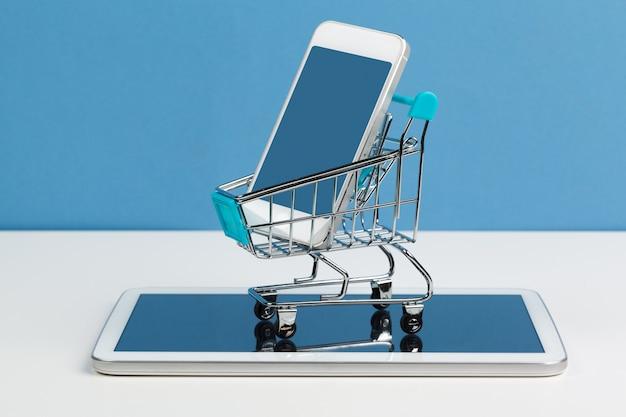 Smartphone con il carrello su fondo bianco Foto Premium