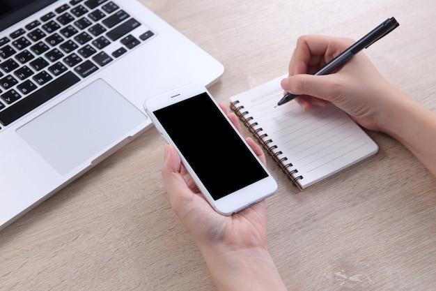 Smartphone del modello della tenuta della donna di affari con la scrittura sul taccuino Foto Premium
