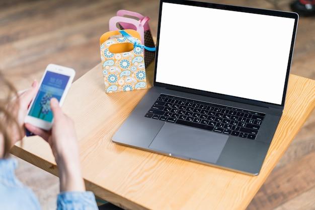 Smartphone della holding della mano della femmina con il computer portatile dello schermo in bianco sulla tabella di legno Foto Gratuite