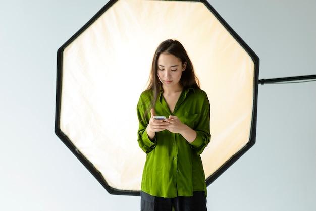 Smartphone della tenuta della donna del colpo medio Foto Gratuite