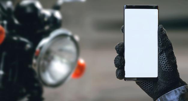 Smartphone della tenuta della mano del motociclista con lo schermo in bianco. Foto Premium