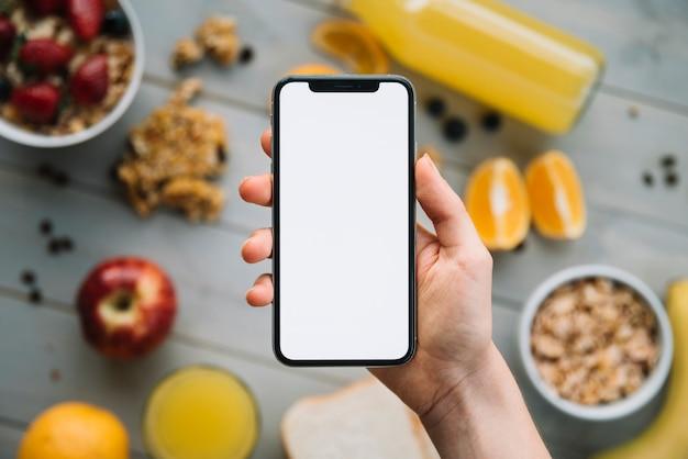 Smartphone della tenuta della persona con lo schermo in bianco sopra la tavola con i frutti Foto Gratuite