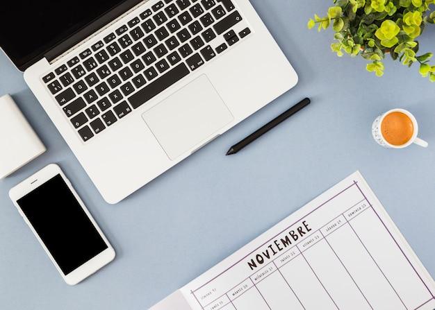 Smartphone e laptop con il taccuino sulla tavola blu Foto Gratuite