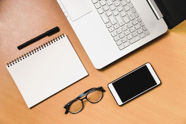 Smartphone e taccuino del lwith del taccuino del computer di affari sullo scrittorio di legno Foto Premium
