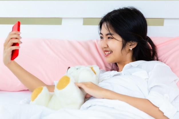 Smartphone femminile di uso dell'adolescente sul letto Foto Gratuite