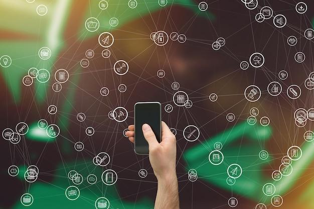 Smartphone holding della mano con la raccolta di icone Foto Gratuite