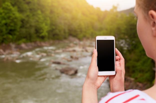 Smartphone in mano della donna, il fotografo fa foto di bella natura, schermo vuoto sul dispositivo. Foto Gratuite