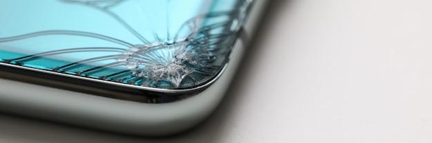 Smartphone moderno che si trova alla tavola con la crepa nell'angolo Foto Premium