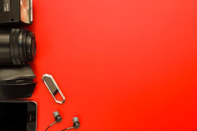 Smartphone vicino a attrezzature fotografiche, mouse del computer, unità flash e auricolari Foto Gratuite