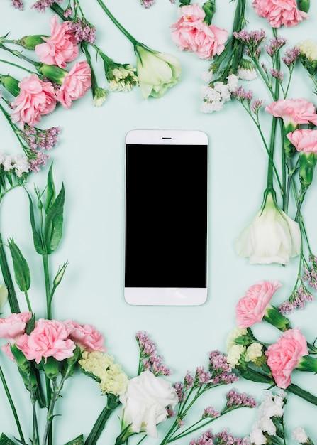 Smartphone vuoto circondato da limonium fresco; garofani e fiori di eustoma su sfondo blu Foto Gratuite
